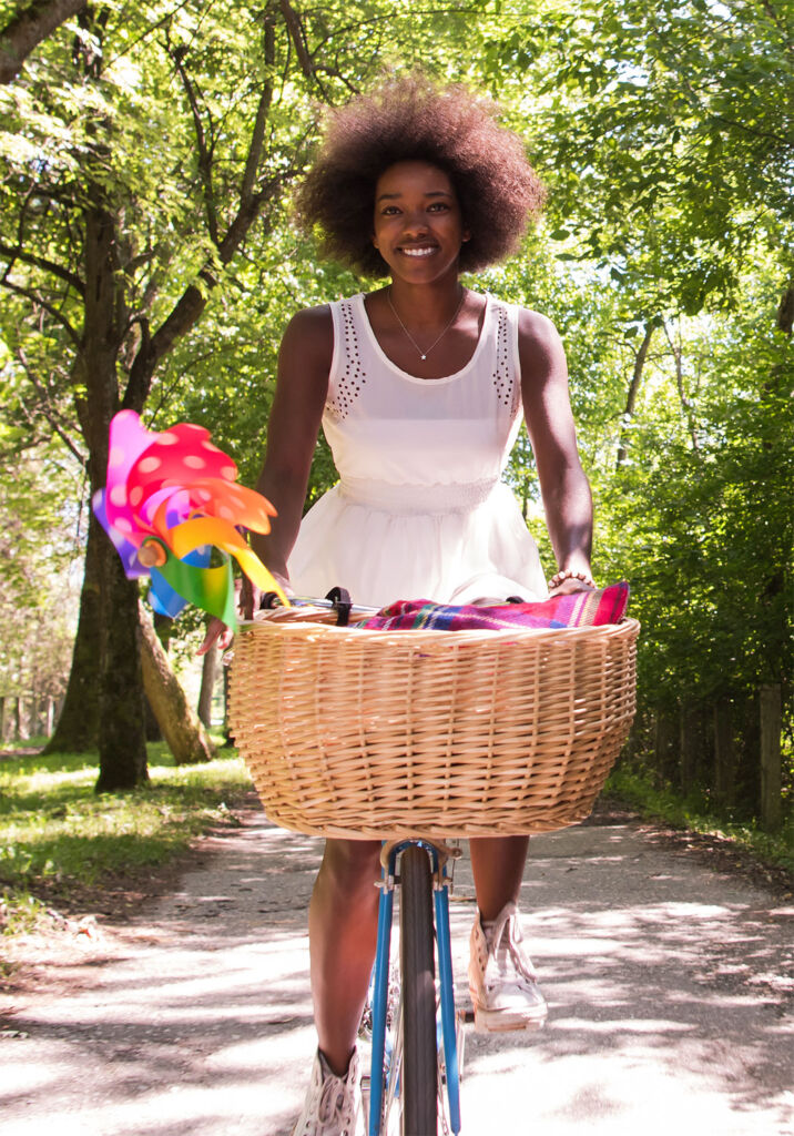 A woman enjoying a bicycle ride with a basket of colourful flowers on the front in the countryside