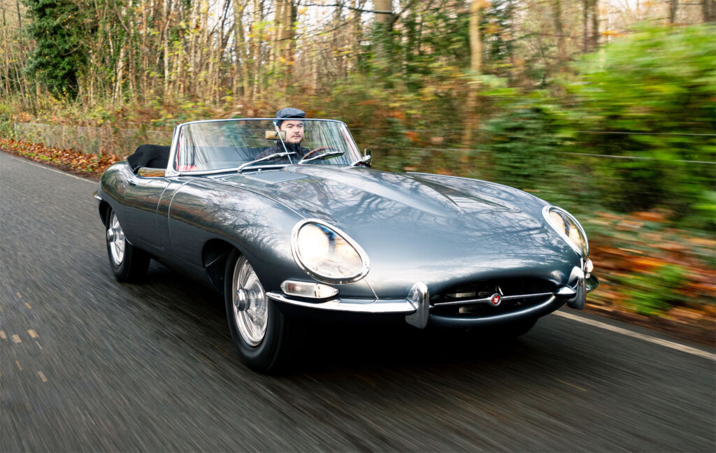 Driver enjoying a jaunt out in a E-Type Jaguar along country roads