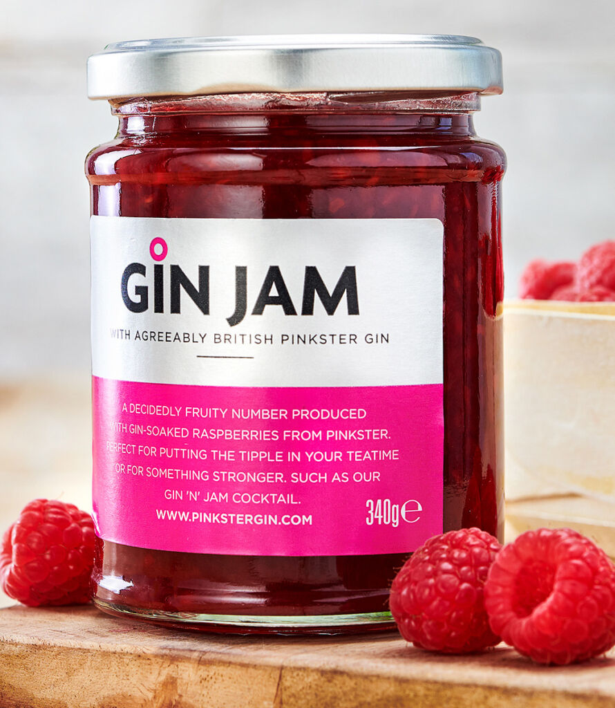 A jar of Gin Jam on a wooden work surface with some berries