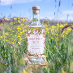 Bottle of Otterbeck Cotton Gin in a wildflower meadow