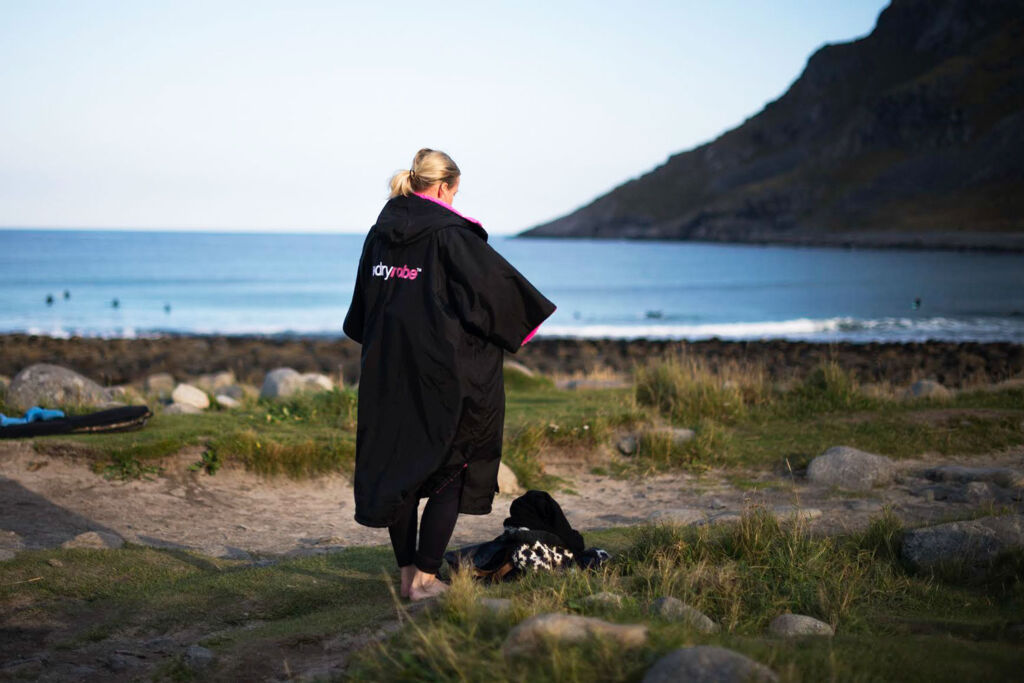 Female surfer wearing a pink and black dryrobe by the beach