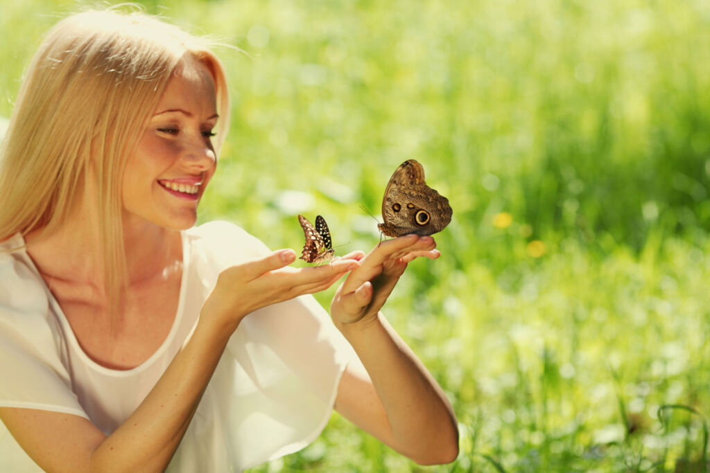 A woman outside with a butterfly sat on her finger