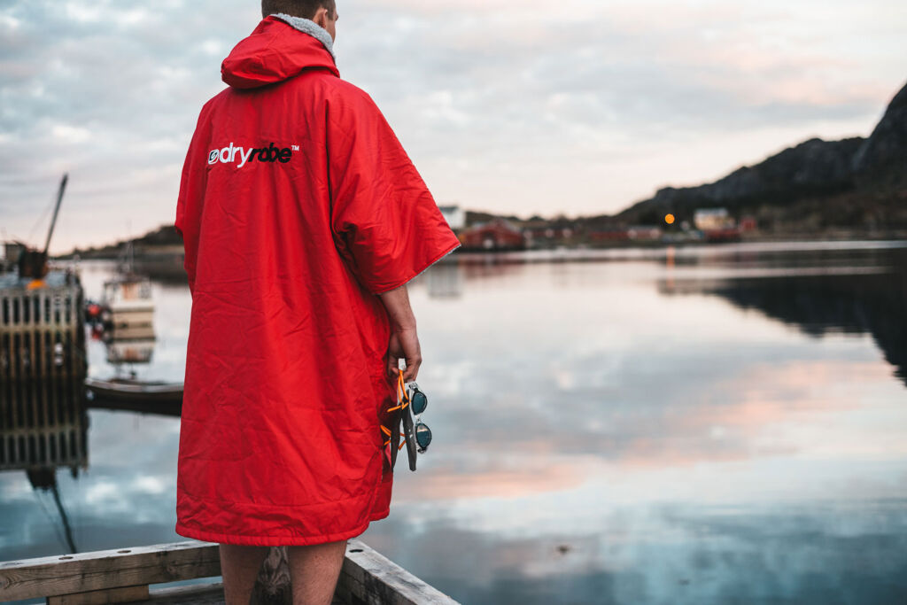Man wearing a short sleeve red dryrobe by a lake