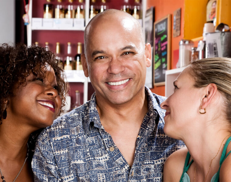 A man with a great natural smile with two women admiring it
