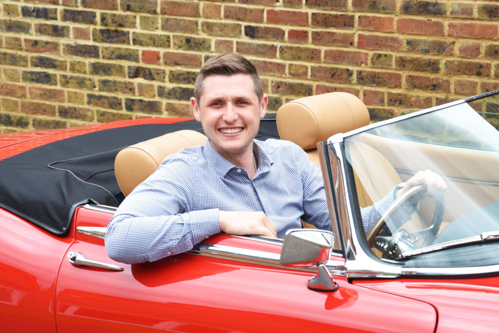 Marcus Holland sat in a red E-type Jaguar