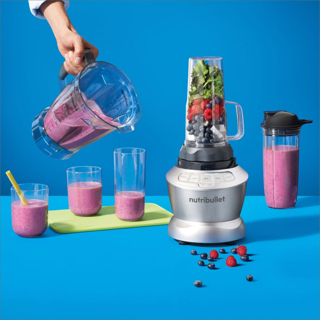 Image showing a woman pouring a smoothie from the larger jug which comes with the NutriBullet Blender Combo