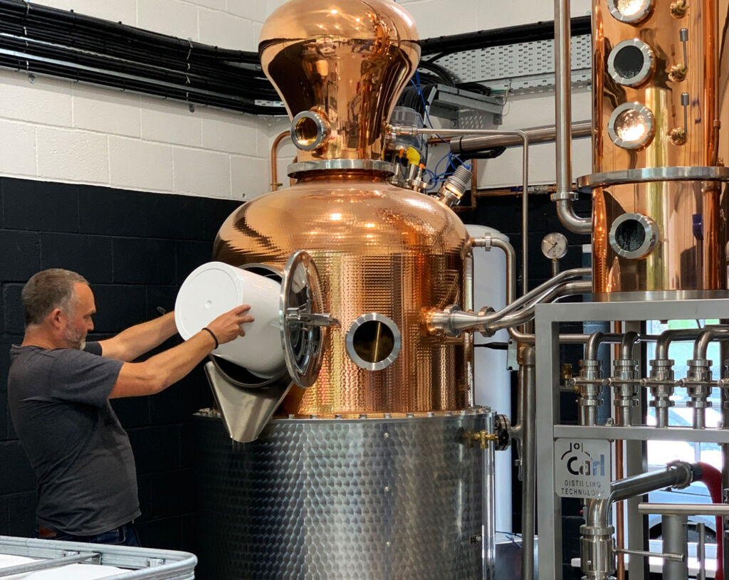 Otterbeck's co-founder and distiller, Chris feeding Eliza, the copper still