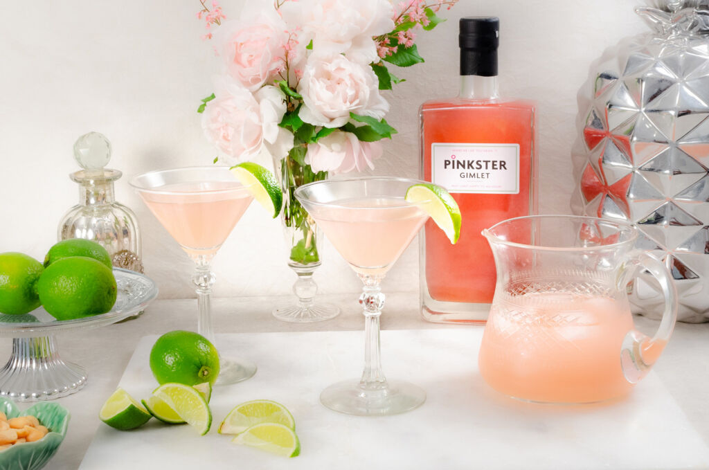 Two glasses and a jug filled with Pinkster Gimlet