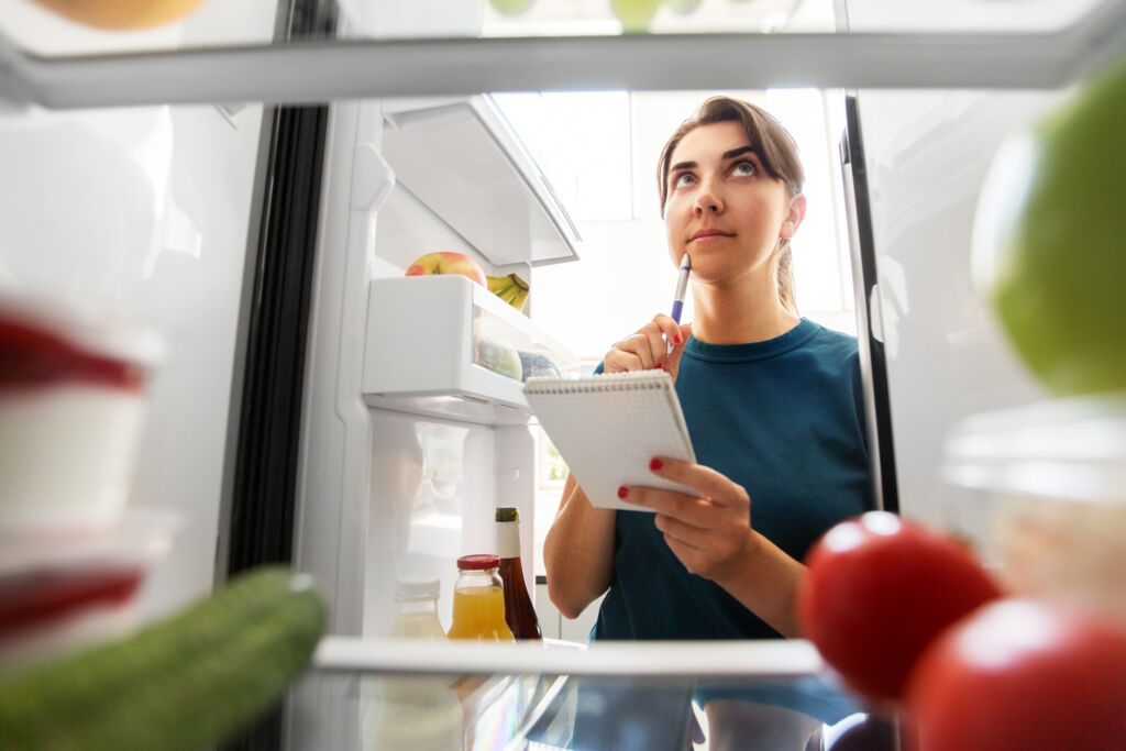 A young woman contemplating what food to put in a fridge