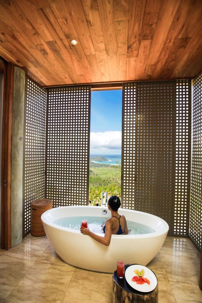 Woman enjoying stunning views over the sea from a bathtub