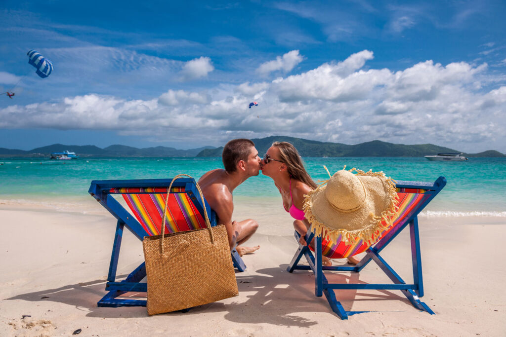 A young couple sharing a kiss sat in deckchairs in a beach