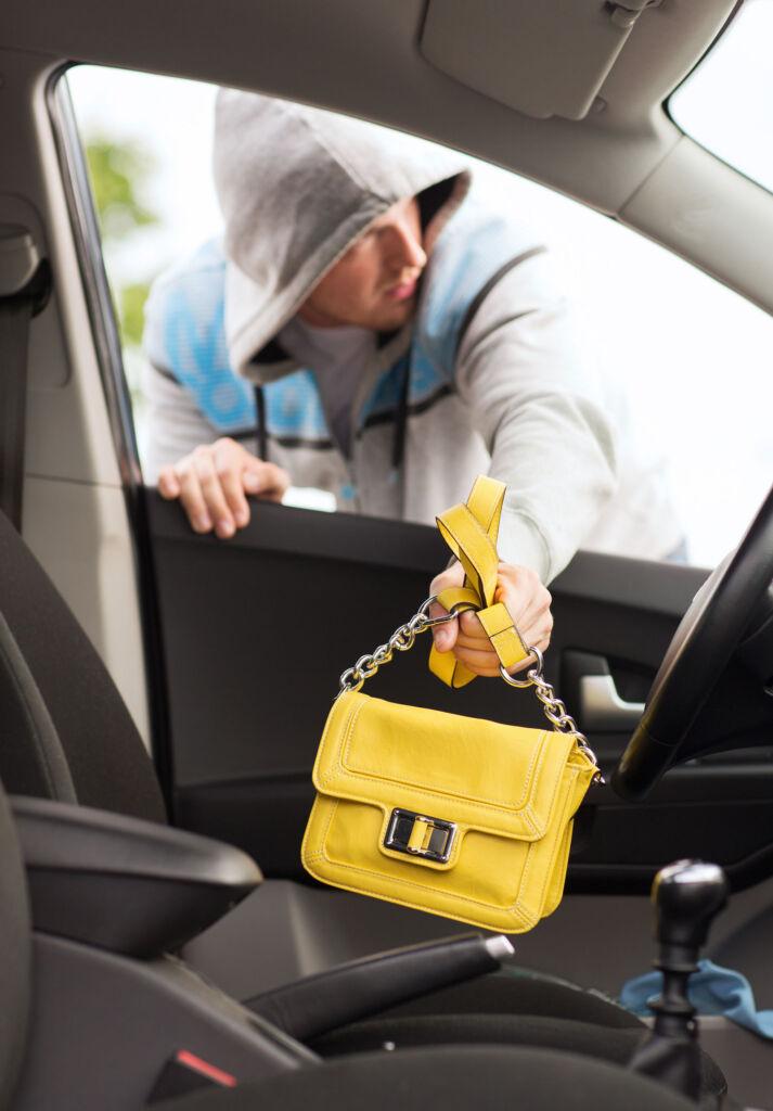 A criminal taking a handbag from a car