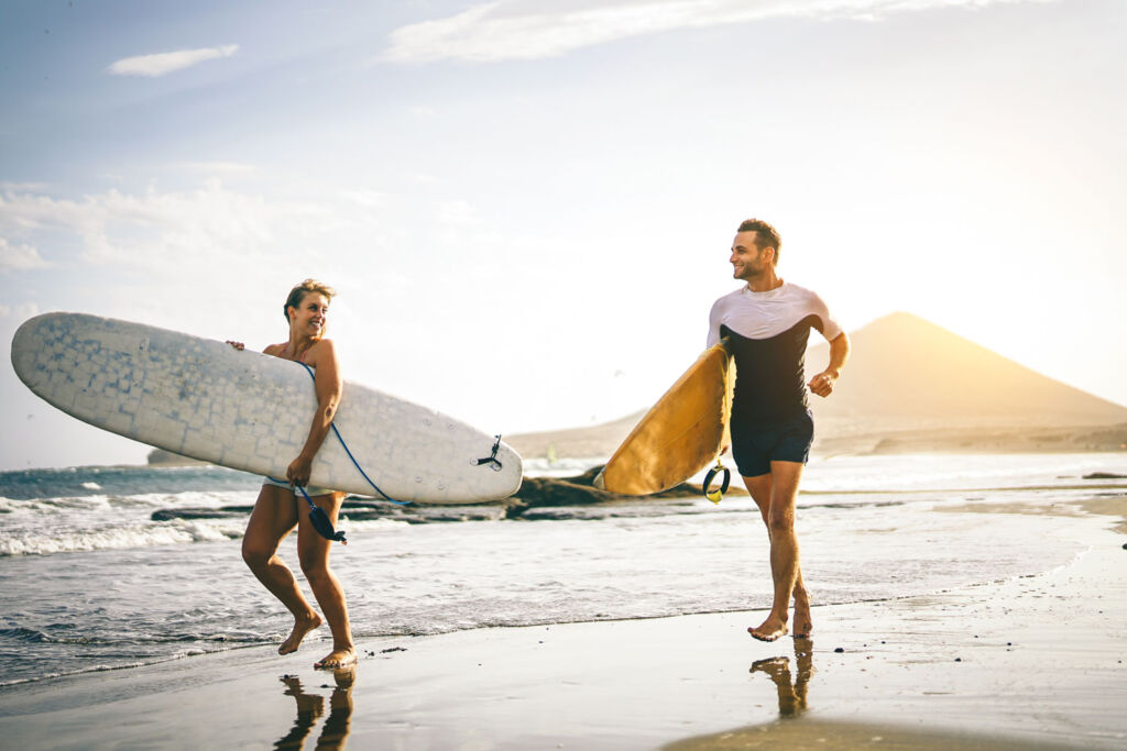 Male and female surfer leaving the sea at Lombok
