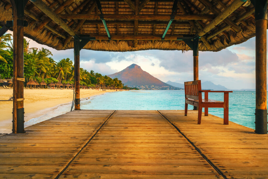 Standing on a jetty in Mauritius looking over a gold sandy beach