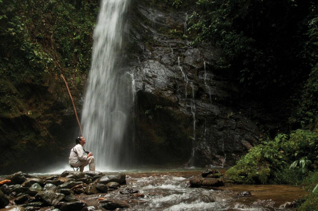 A man on the Forest-to-Coast experience by a waterfall near Mashpi-Lodge