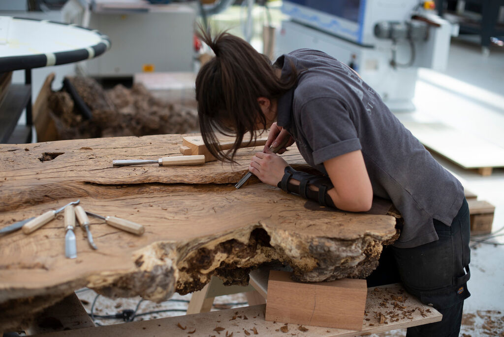 One of the craftspeople carving into a large piece of reclaimed wood