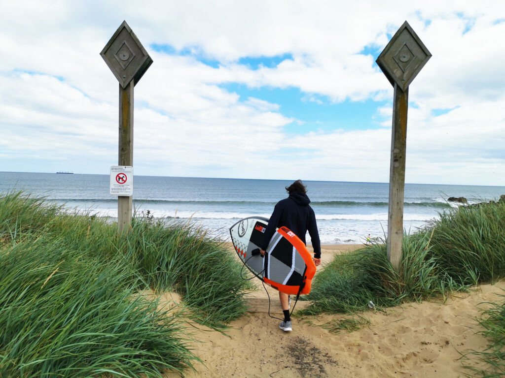 A man carrying his board down to the English seashore
