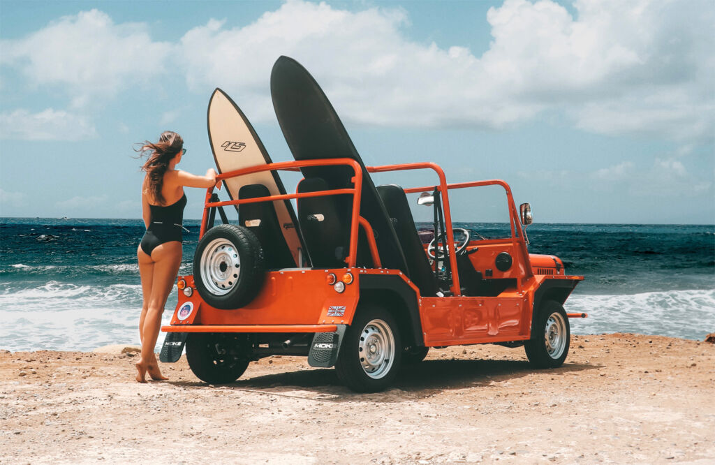 A young swimsuit clad woman on a beach with a MOKE carrying some surfboards