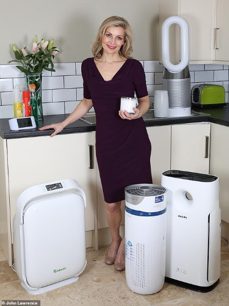 A woman standing with some of the air purifiers from Meaco