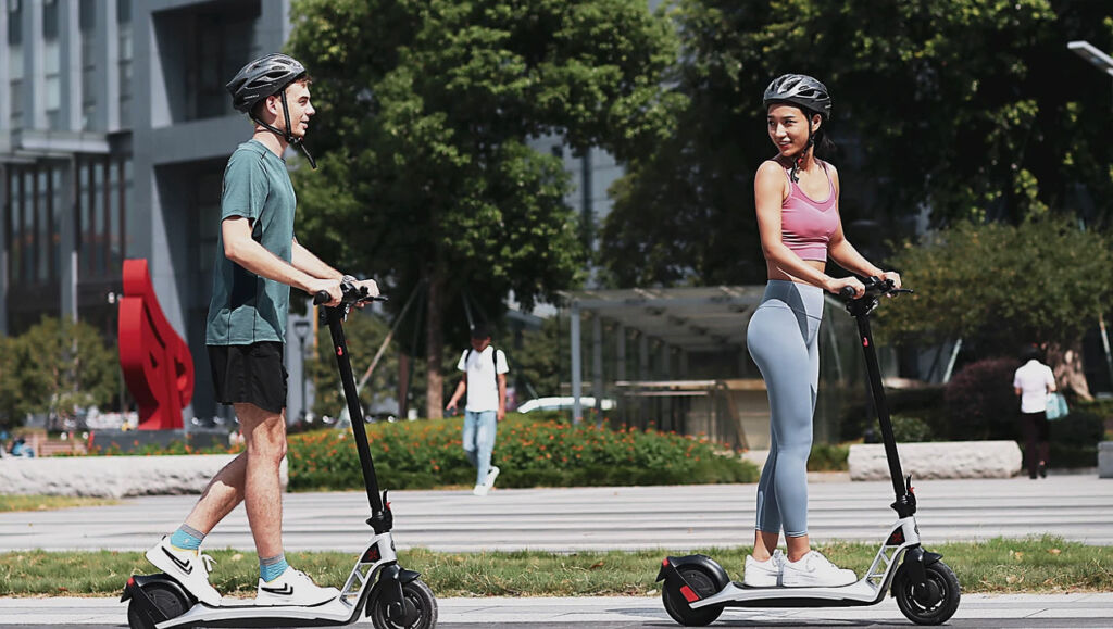 Young people riding the i1 electric scooter