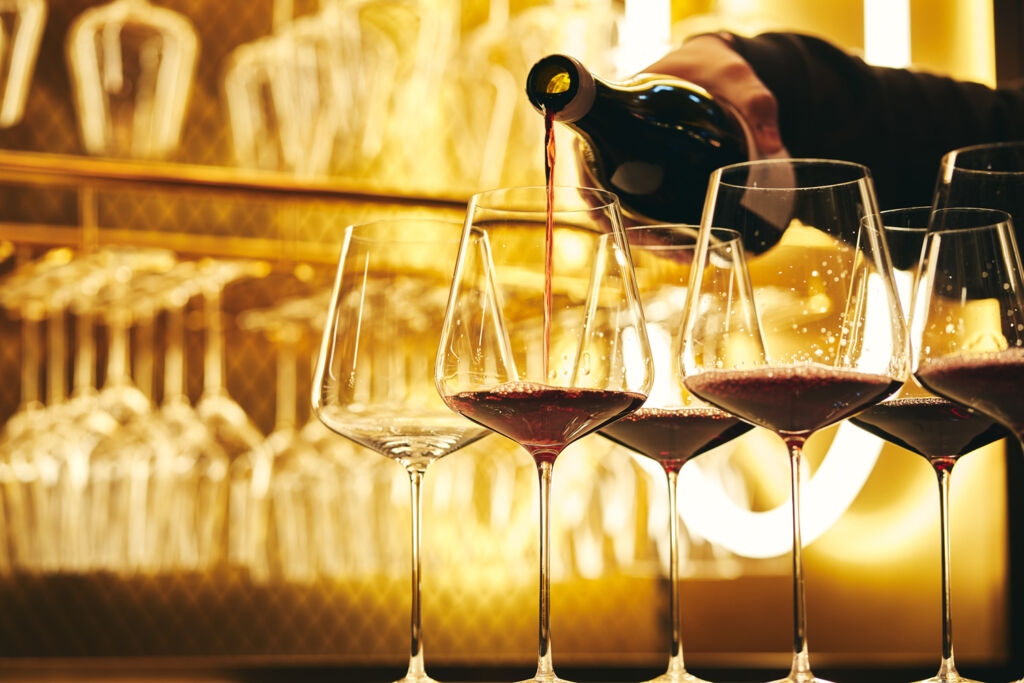 A sommelier pouring red wine into some empty glasses