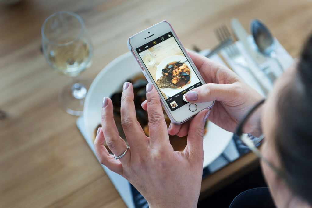 Someone taking a photograph of a dish with their mobile phone