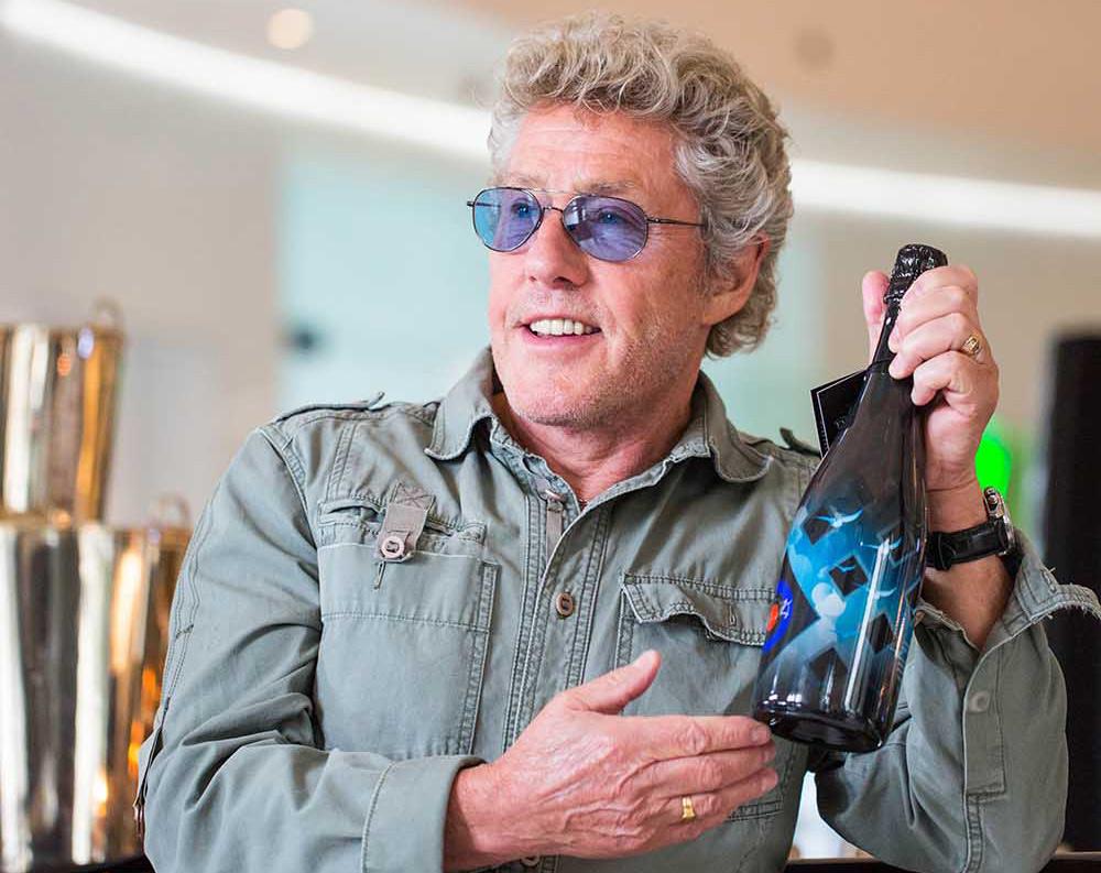 Roger Daltrey proudly holding a bottle of Champagne Cuvée Roger Daltrey