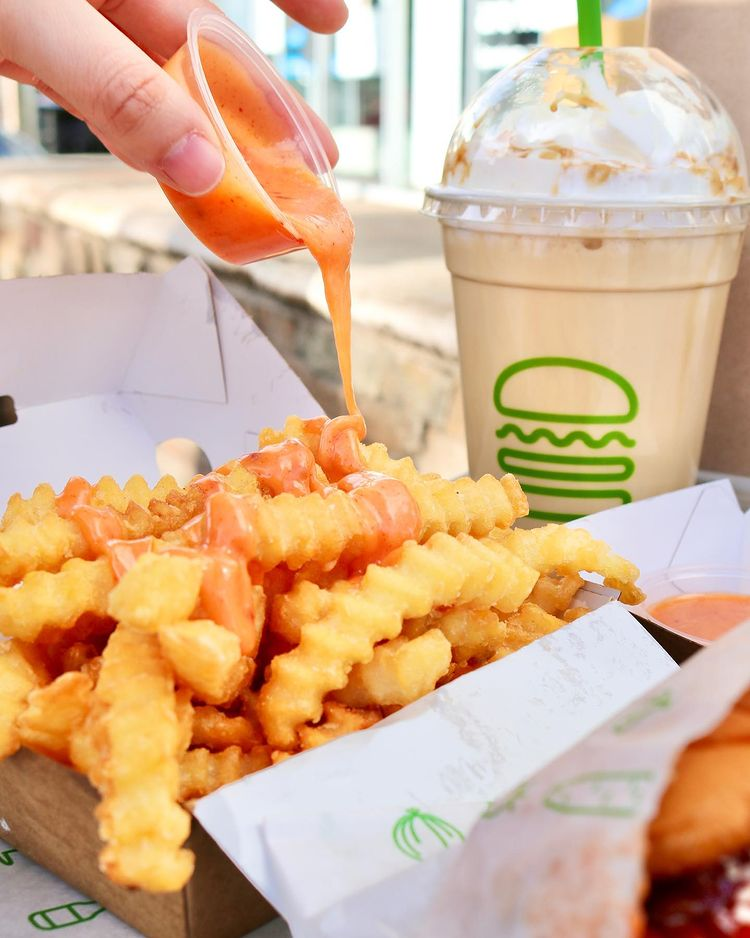 Some of Shake Shack's delicious fries with sauce being poured on them
