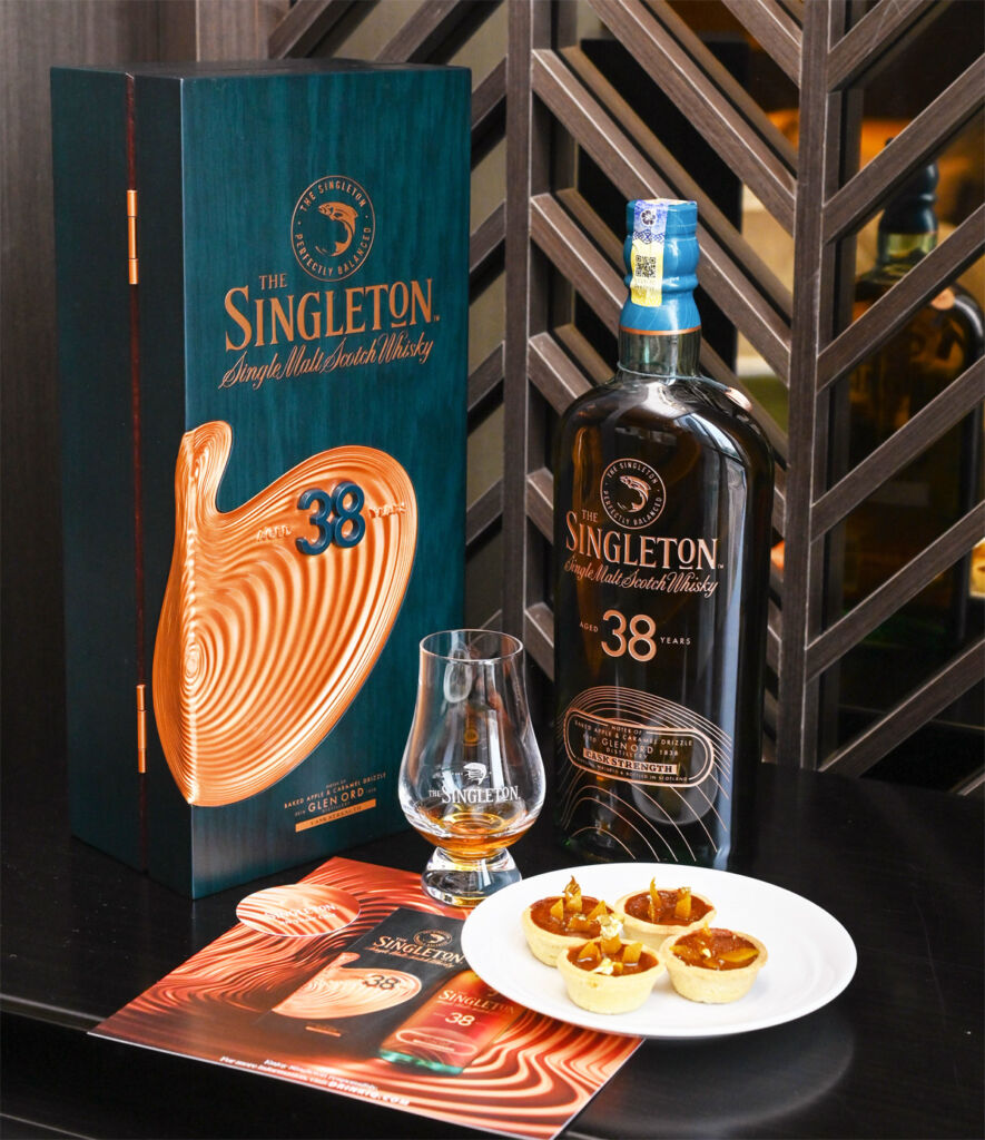 A bottle of the whisky on a table with some canapes