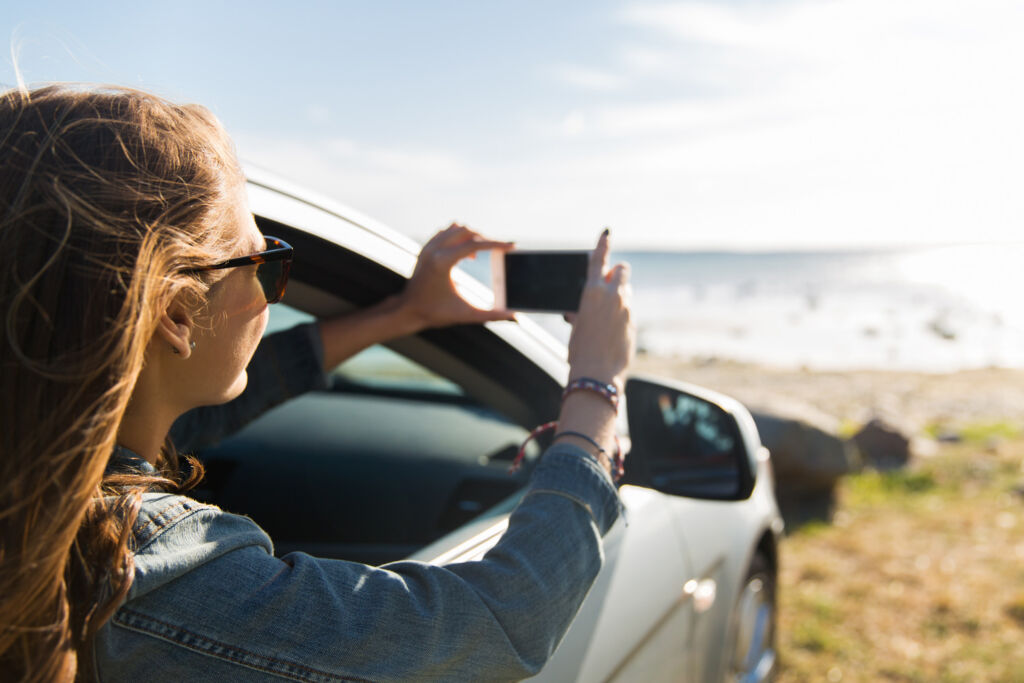 A woman taking photos of Britains coastline from her car