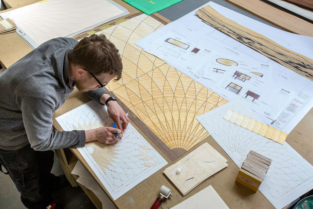 One of the designers working on a wooden marquetry pattern