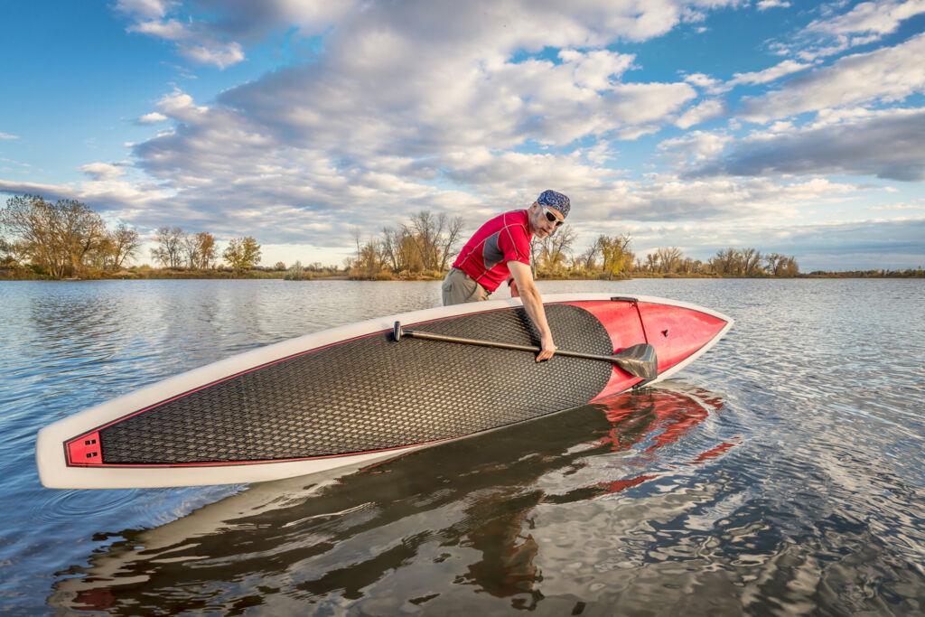 A man taking his hard-board into a lake