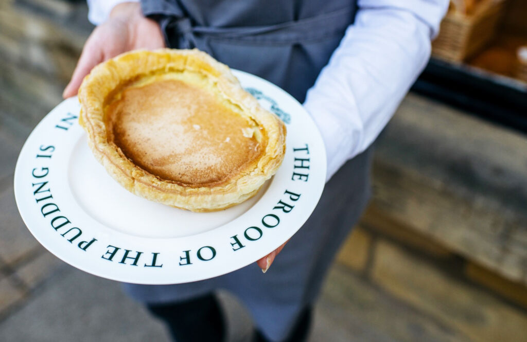 Someone carrying an authentic Bakewell Pudding on a plate