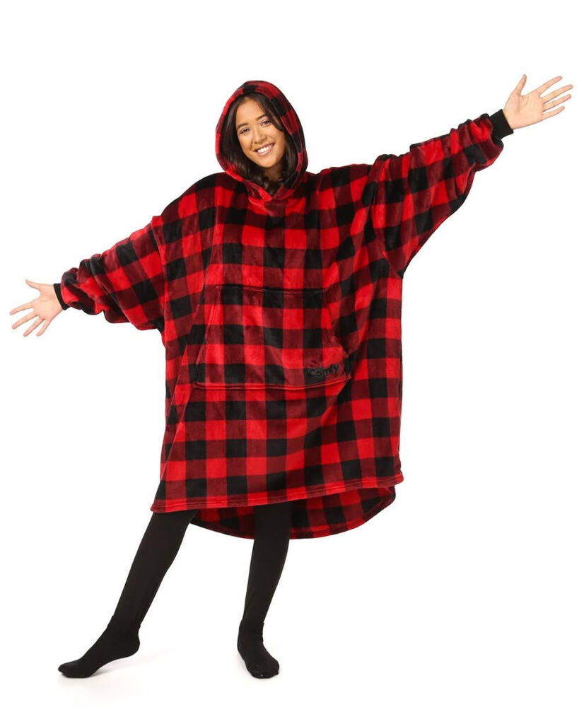 Young woman wearing a red check comfy wearable blanket
