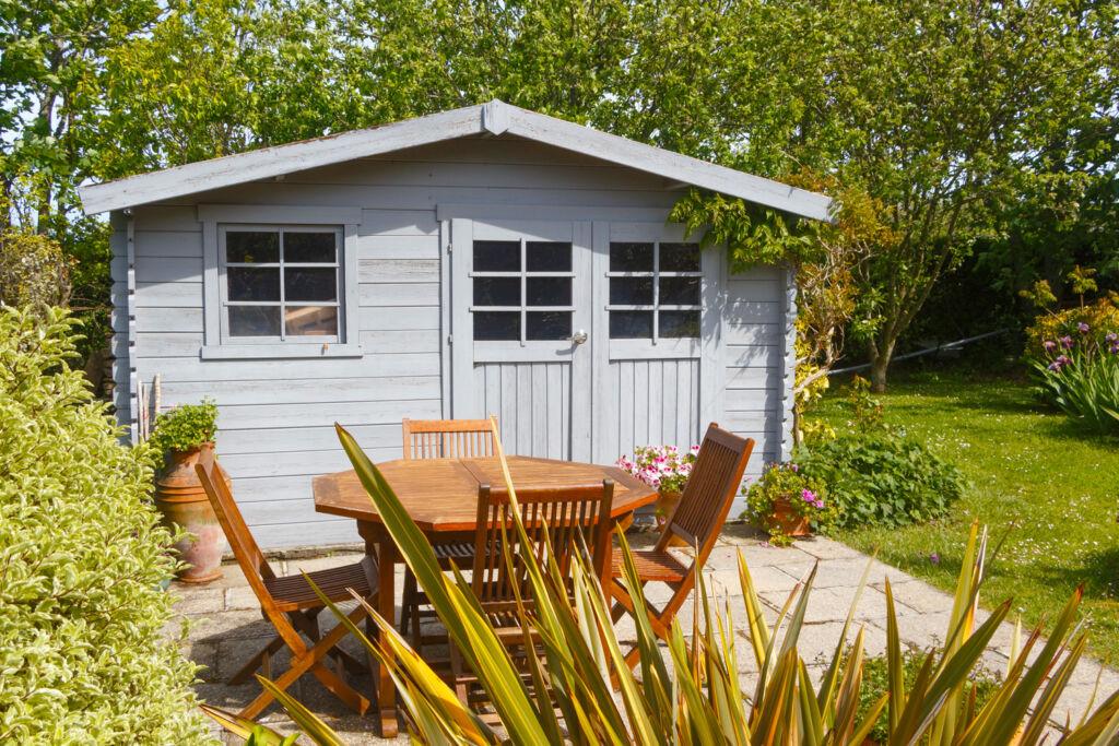 A grey summerhouse in a vibrant garden
