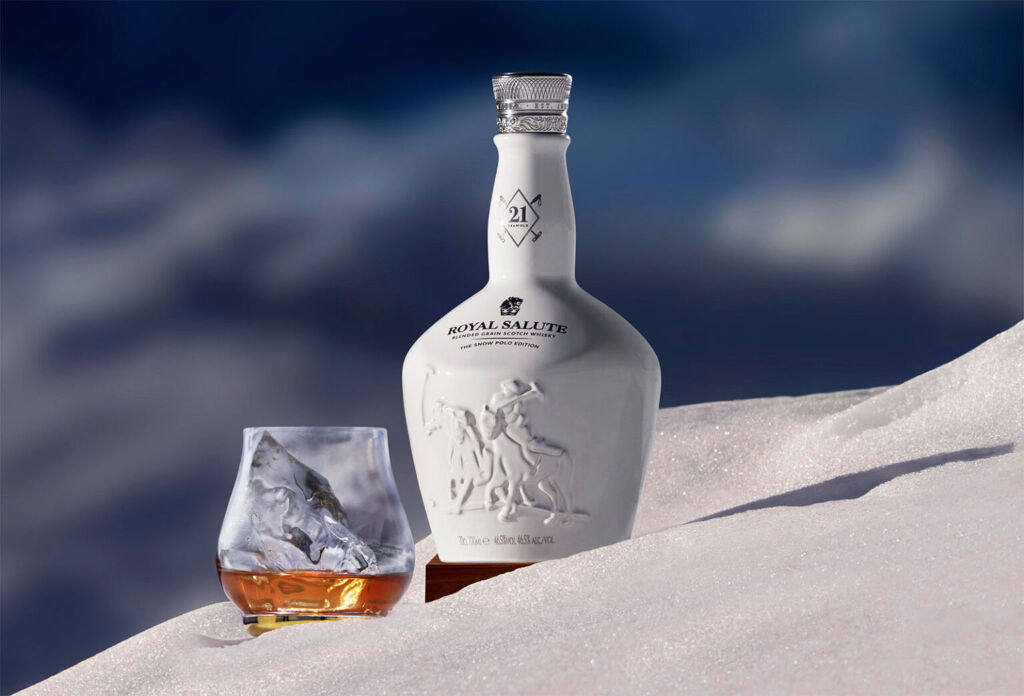 A glass and a bottle of the Snow Polo Editon in fresh snow