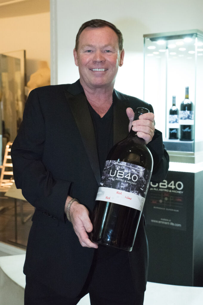 Ali Campbell holding a huge bottle of the bands Red Red Wine