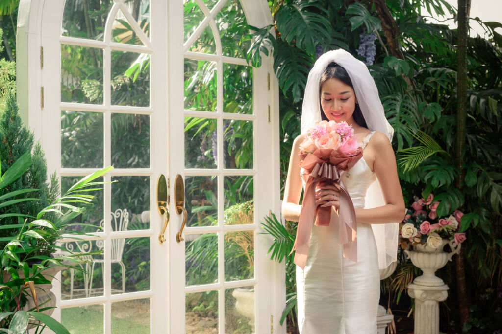 A young Asian woman holding a bouquet at a wedding