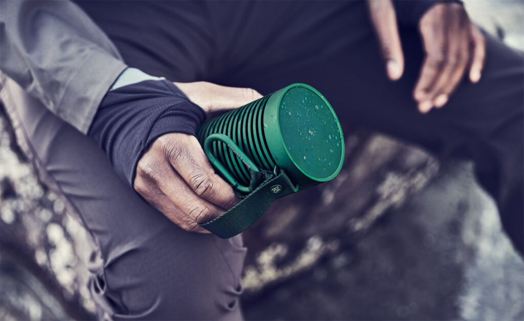 The Bluetooth speaker in green colour being held in the hand