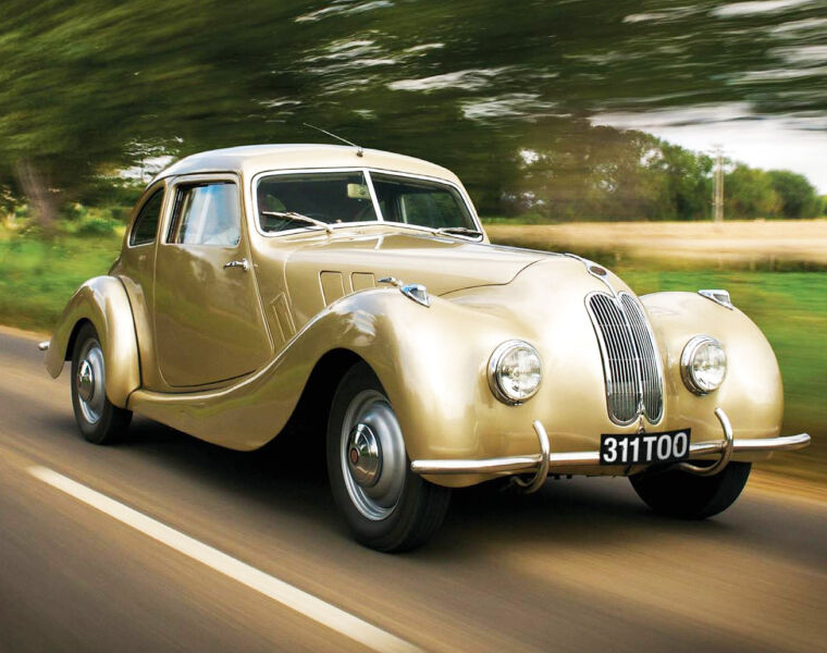 A classic Bristol Car in gold paint driving along country roads