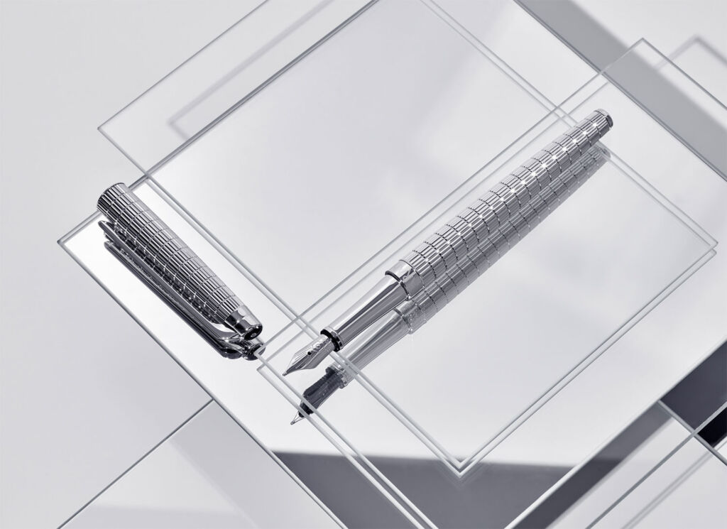 The fountain pen laid out on a mirrored table with its cap next to it