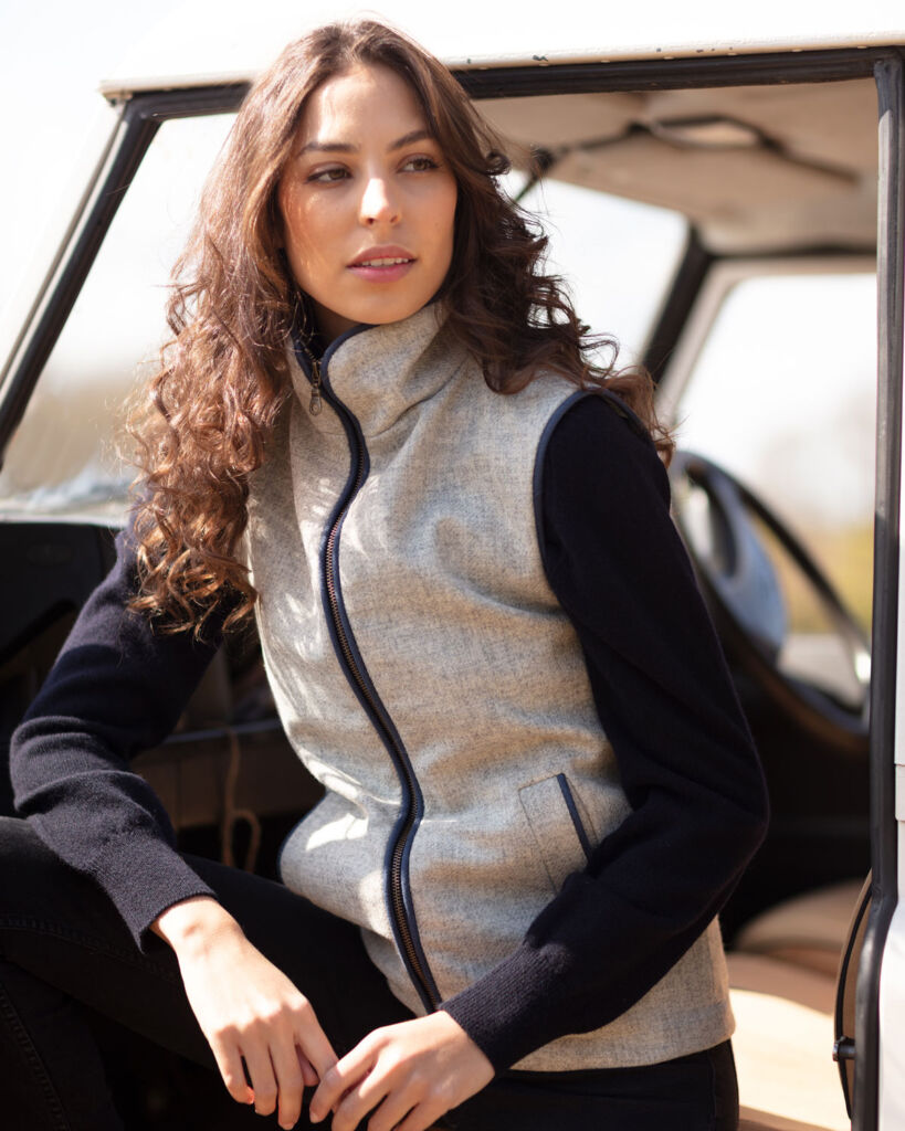 Model sat on a car seat wearing the Frimble tweed fitted waistcoat