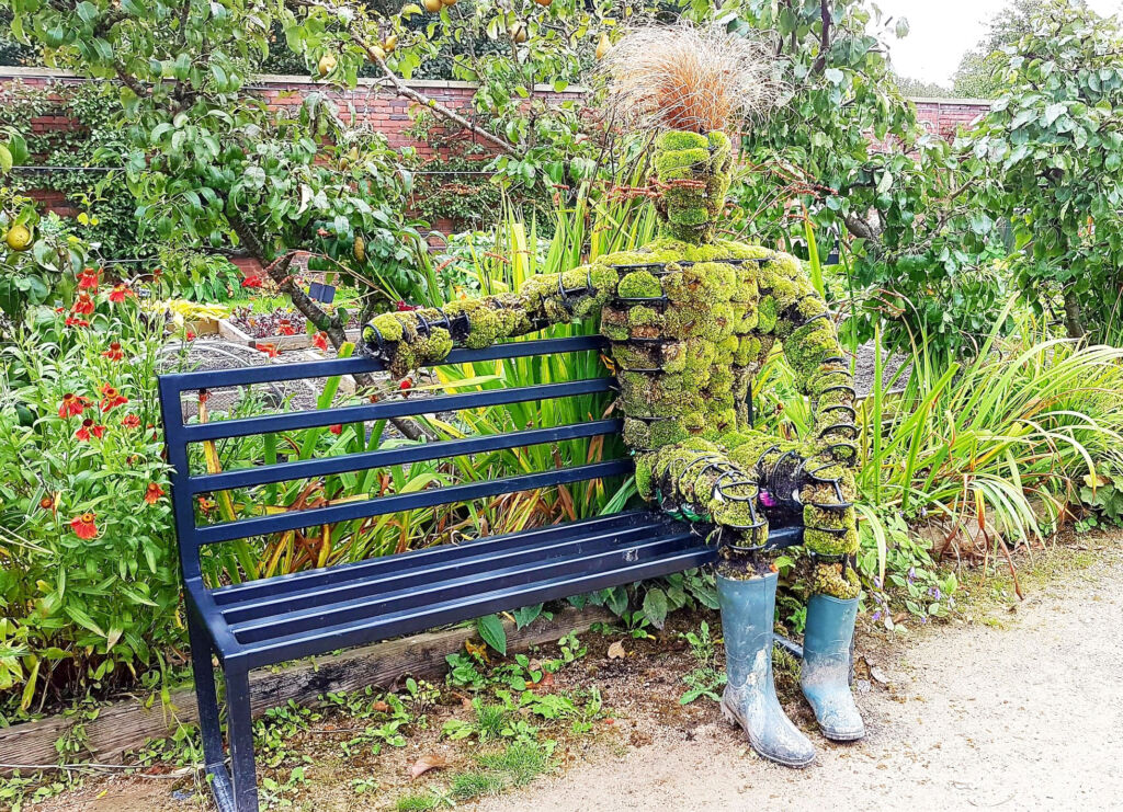 A person made from wild foliage sitting on a metal bench