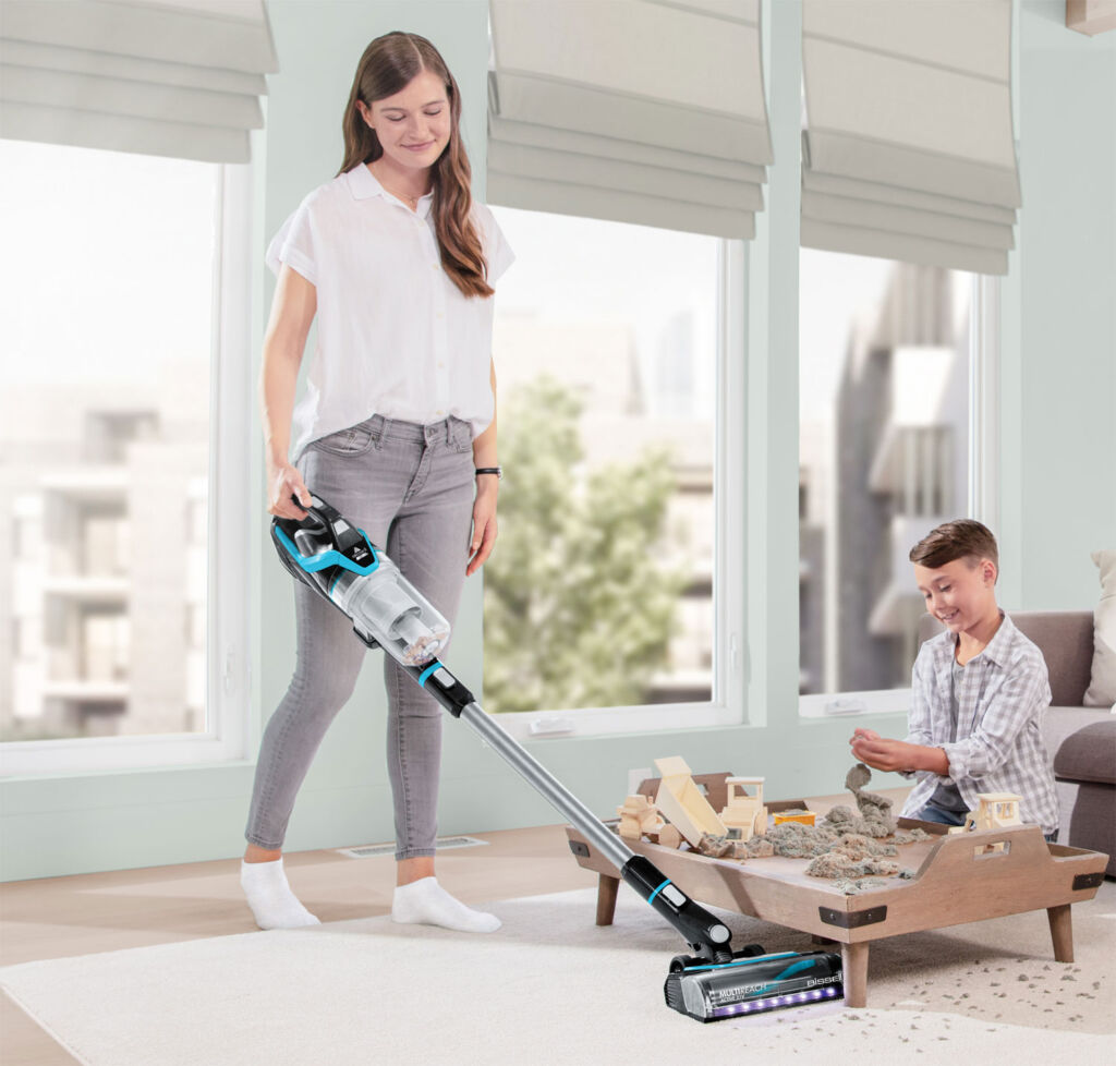 Woman using the Bissell cleaner in her home as her son plays with his toys