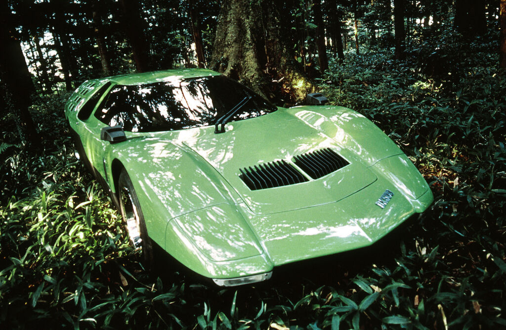 A light green coloured version of the car parked in a dark forest