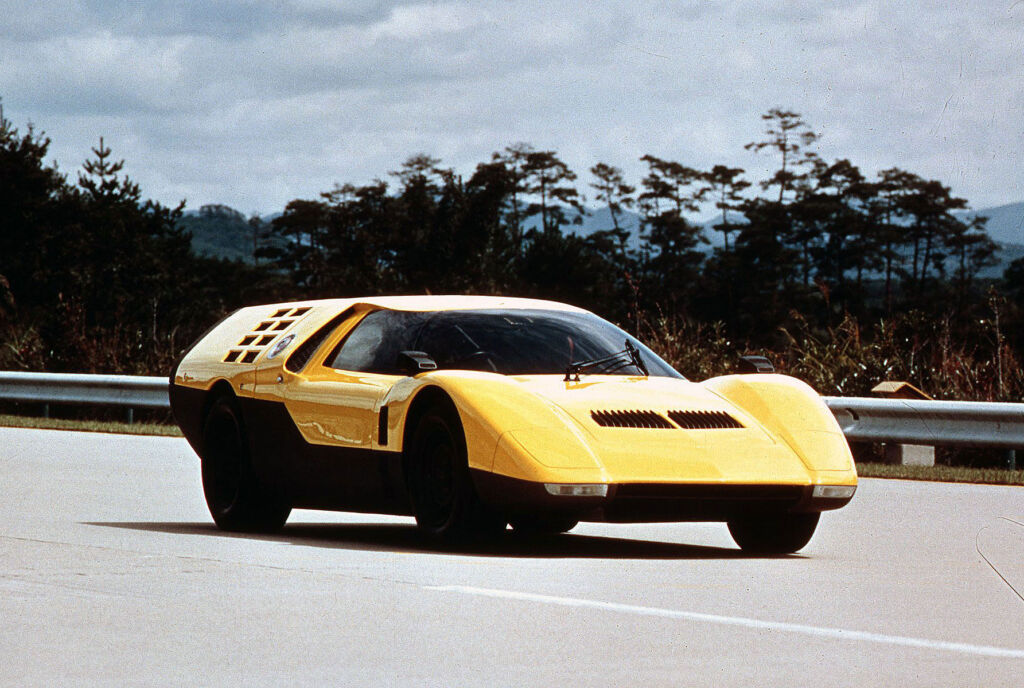 Mazda RX500 in yellow being driven on the road