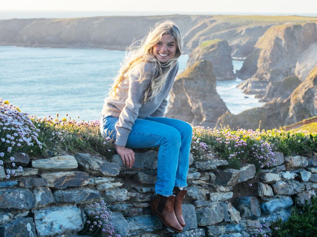 Model wearing a Tom Lane jumper sat on a rock wall overlooking the sea