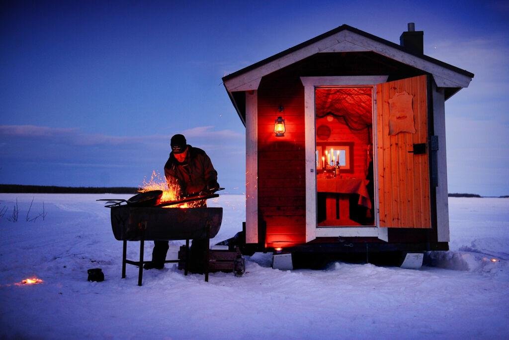 Preparing the Aurora Hideaway dinner on the snowy landscape in Swedish Lapland