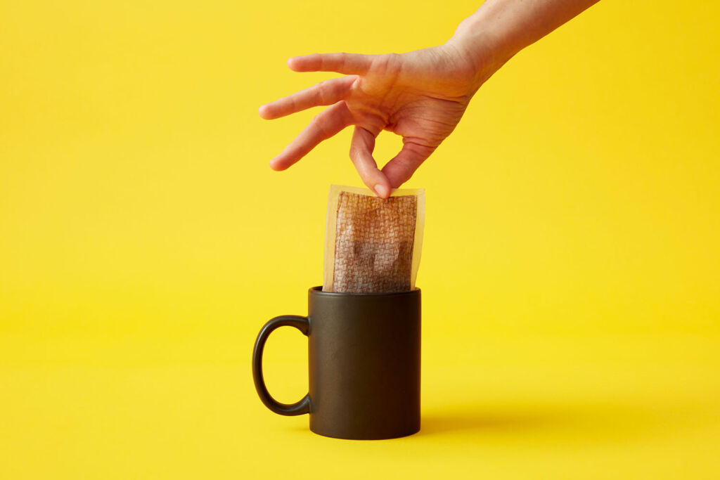 A large Faff coffee bag being removed from a cup