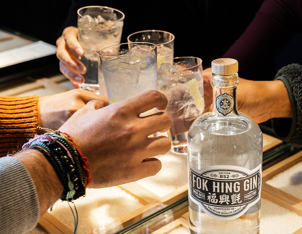 Some people raising some glasses of Fok Hing Gin at a get together